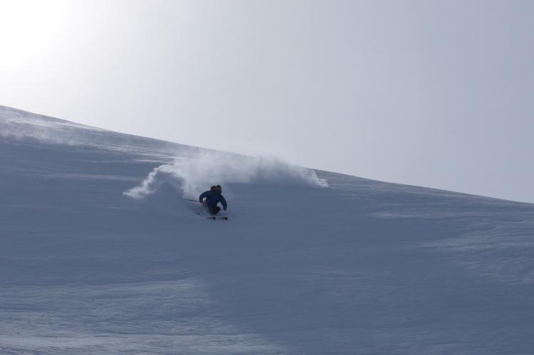 Votre guide joue dans la neige fraîche
